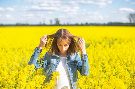 young girl standing in rape field Stock Photo
