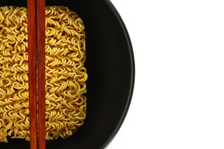 Instant noodles in bowl and chopsticks on white background photo