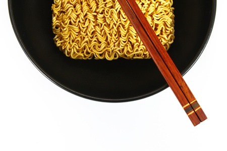 dry noodles in bowl and chopsticks on white background photo