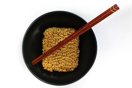 Instant noodles in bowl and chopsticks, close - up photo