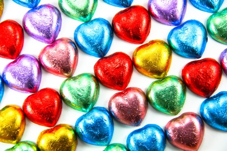 Wrapped colorful chocolate hearts in a row photo