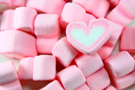sweet hearts shaped marshmallows on pink background photo