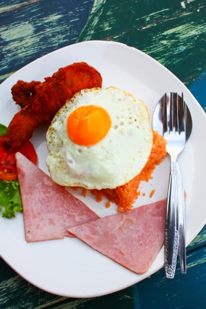 American fried rice with fried chicken, egg and sausage on table Stock Photo