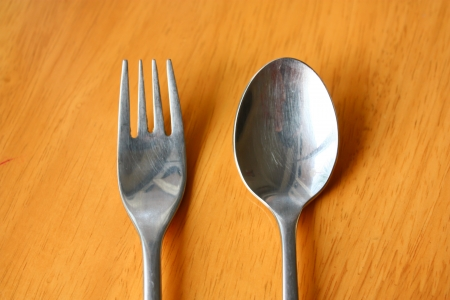 Spoon and Fork on a wood table Stock Photo