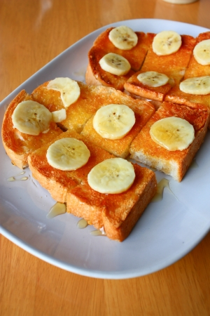 bread toast with honey and banana on plate Stock Photo