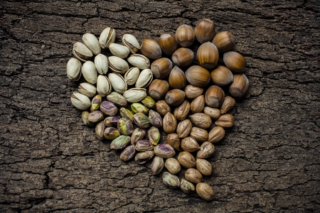 mixed nuts: Heart - shaped nuts: hazelnuts and pistachios Stock Photo