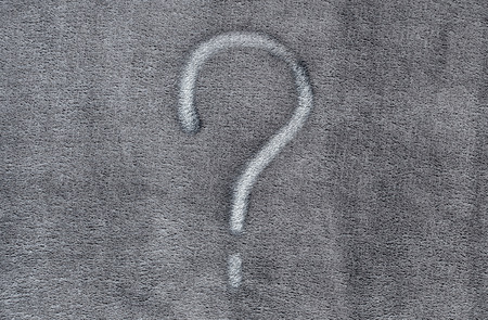 Question mark on gray fabric texture background
