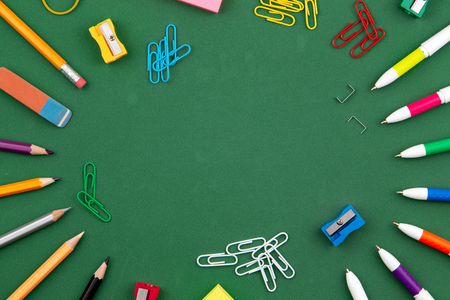 School stationery lies on a green school board forming a frame for text. near pencil and crumpled pages. Copy space Flat lay Top view Concept Education.