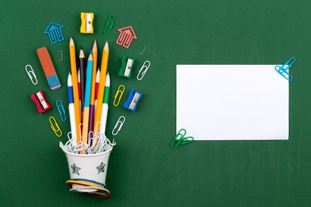 Stationery Pencils paper clip pen eraser in a white bucket. Still life on green school board background. Copy space Flat lay Top view Concept Education.
