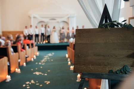 Blur Wedding ceremony in the church building. In the foreground stands a wooden easel with space for text