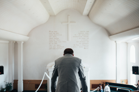 Wedding photo of emotions of a bearded groom with glasses in a gray jacket in the church building.