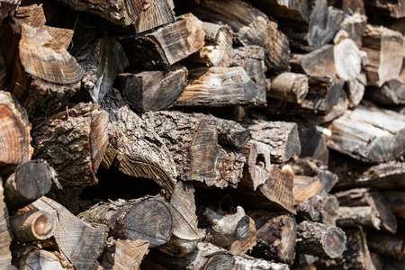 Background from stacked old brown stab wooden logs. Banco de Imagens