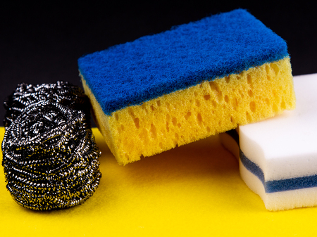 Dishwashing concept. On a black background, different washcloths and scrubbers for washing dishes. Stock Photo