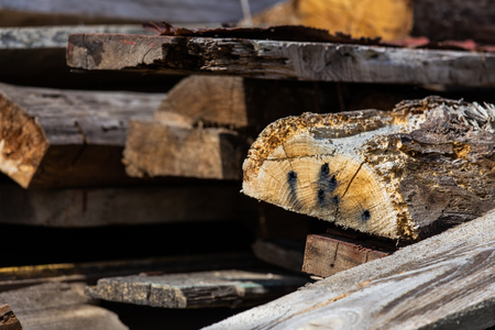 A stack of old wooden planks that lie on the ground Imagens