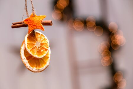 Hanging Christmas decoration of dried oranges, tangerine and cinnamon stars with copy space for text. holiday concept. blurred background.