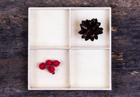 A white box with compartments on a wooden background filled with tree cone and rowan berries.
