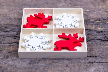A white box with compartments on a wooden background filled with red christmas deer toy and white snowflakes.