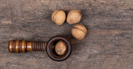 Organic walnuts with nut cracker on a wooden table, wooden background. Crushing, healthy. 版權商用圖片