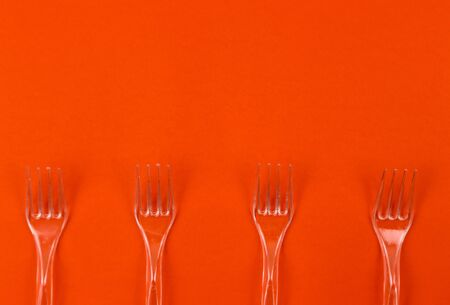 Close-up of clear plastic fork on a orange background. Disposable tableware pattern