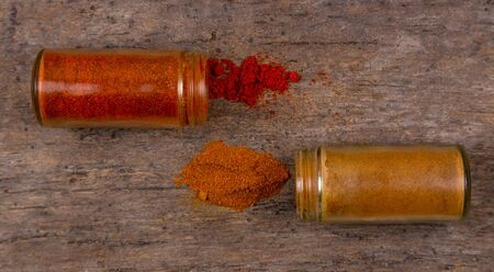 Chilli colorful powder spices scattered from bottle on wooden background