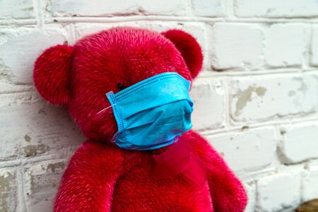 Lonely Red Teddy bear in a protective medical mask on a yellow background with respiratory masks. Coronavirus covid-19 prevention concept. Standard-Bild