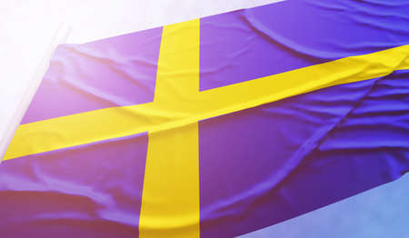 Sweden flag on the blue sky. Close up national flag in bright rays sun that is waving in the wind on flagpole. Stock Photo