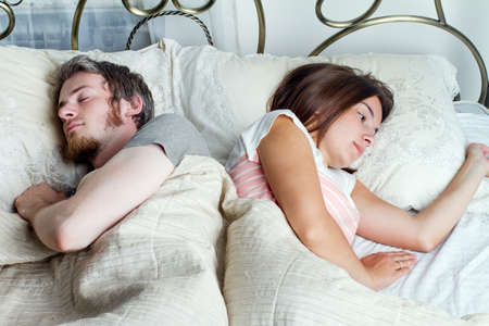 sad young woman lies in bed while her husband sleeps