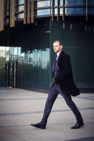 businessman walking outdoors in front of a modern office building Archivio Fotografico