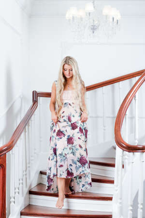 Portrait of young attractive woman going down the stairs