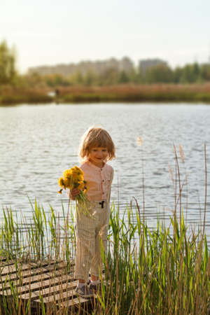 Little boy holding bunch of yellow dandelion flowers in a park, lake or river in the background