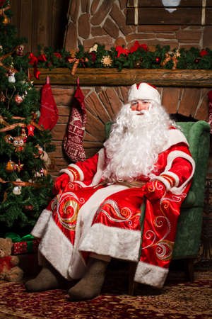 Cheerful Santa Claus sitting at his chair with fireplace and Christmas Tree in the background