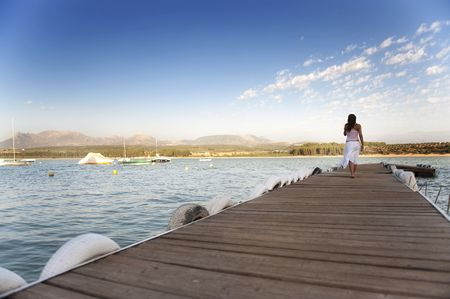 shoeless: Young woman walking over pier and the blue sky