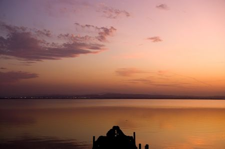 Silhouette of a kissing couple on pier at sunset photo