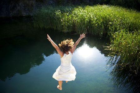 Mujer joven en vestido blanco saltando en un idílico lago Foto de archivo