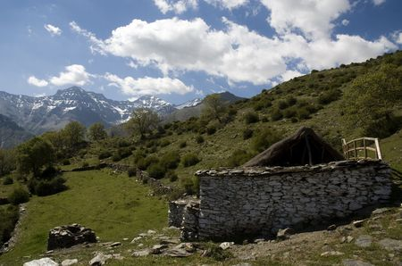 Abandoned farmhouse in with green meadow against highest spanish mountains  photo