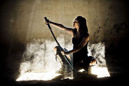 Beautiful woman posing with katana sword.  photo