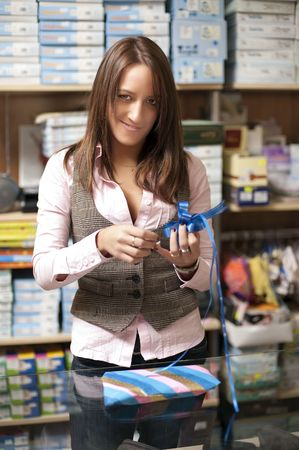 saleswomen: Beautiful young shop assistant wraping a gift