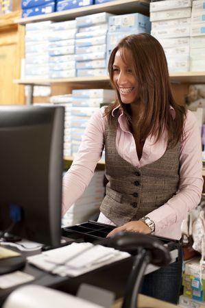 shop assistant: Beautiful young shop assistant at cash Stock Photo
