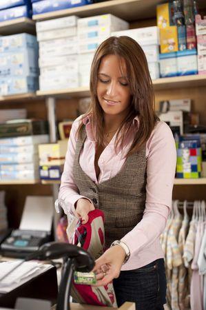 saleswomen: Young beautiful shop assistant at cash Stock Photo