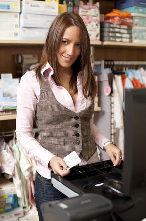 saleswomen: Young beautiful shop assistant at cash Stock Photo