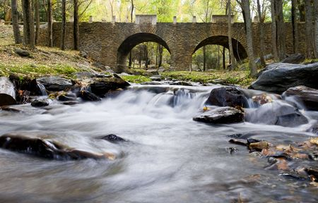 Beautiful old stone bridge over stream water, long exposure  photo