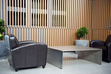 Luxury waiting room with plants against wooden wall photo