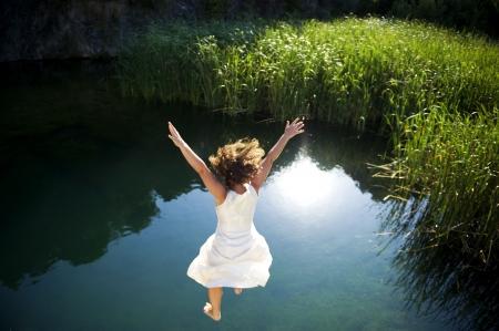 Mujer joven en vestido blanco saltando en un lago idílico  Foto de archivo