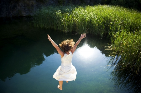 lake shore: Young woman in white dress jumping into a idyllic lake