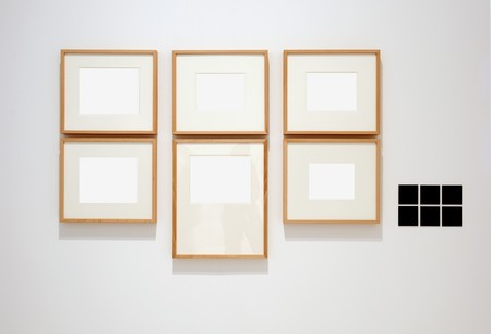 Six empty frames on white wall in museum with labels  photo