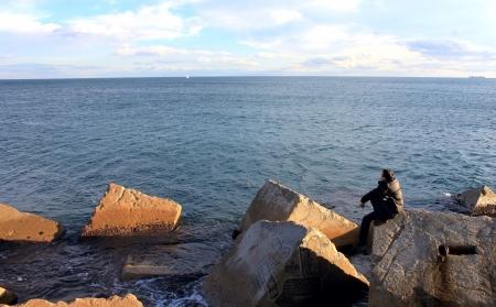 Man zit op de grote steen in de richting van de zee