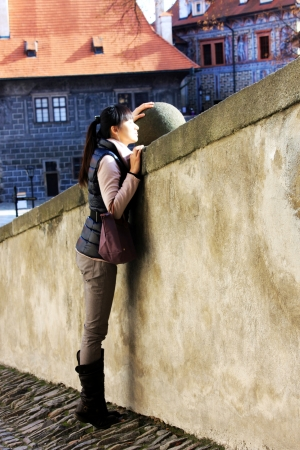 Lovely girl tiptoe in a old town and try to find something interesting Stock Photo - 16948729