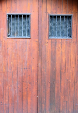 closed community: Wooden door with iron windows Stock Photo