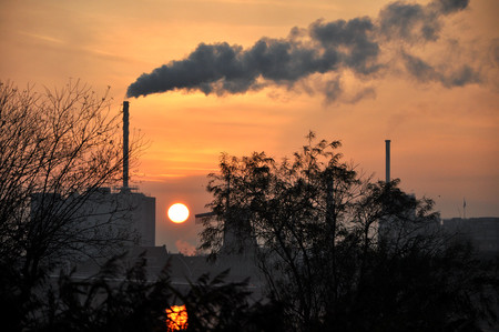 Horizon industry in a small netherland town in Europe, with a big chimney and smoke, sunset and sun as background