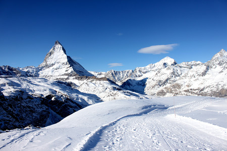 Scenic view on snowy Matterhorn peak in sunny day with blue sky and some clouds in background. Stock Photo